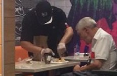 'The cashier came out of the kitchen, sat down, and began helping the man to eat'