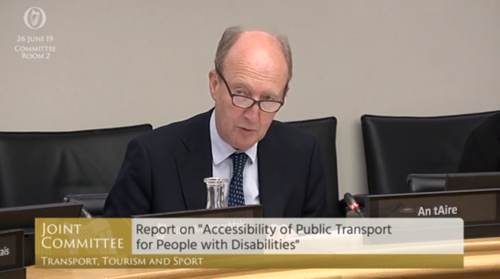 Then Minister for Transport Shane Ross - wearing a dark suit jacket, light shirt and spotted tie - sitting at desk in Committee Room 2 on 29 June 2019, making the announcement of the National Transport Training Centre. His mic is lit up in red showing he is speaking. The text on the Oireachtas TV screen says - Joint Committee, Report on Accessibility of Public Transport for People with Disabilities.