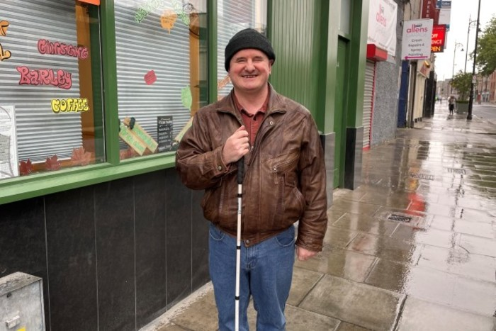 Robbie Sinnott - wearing a cap, brown leather jacket and jeans, carrying a cane - standing on a wet street outside a coffee shop painted in green.