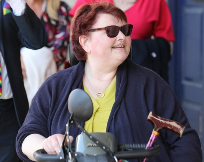 Transport activist Suzy Byrne - mobility scooter user wearing sunglasses, a yellow top and navy cardigan - with people blurred in the background. The top of Suzy's walking stick and mobility scooter are visible.