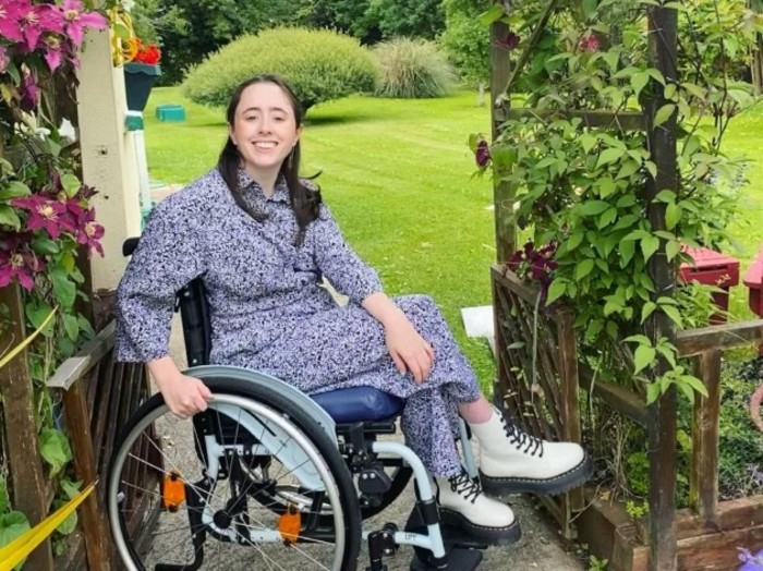 Niamh Ní Hoireahbhaird, a wheelchair user wearing a grey patterned dress and cream Dr Martens boots, in her garden beside a climbing plant with pink flowers.