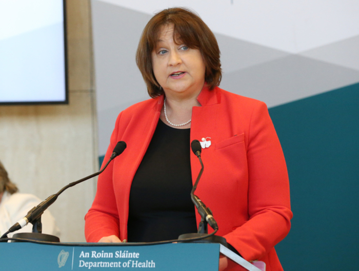 Minister Anne Rabbitte, wearing a black top and red jacket, speaking at a podium with two microphones.