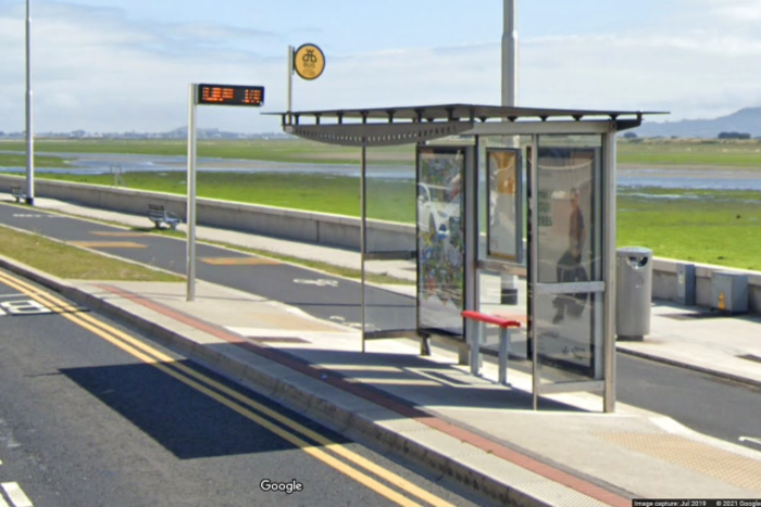 A glass bus shelter beside the sea with advertising on the back panels and a bench with a red top, with a real-time bus display on a pole nearby. The stop is located between the road and a cycle lane. There are two dished kerbs to cross the cycle lane - made of tarmac - from the bus stop to the path - both of which are made of grey concrete. There is no marked crossing on the cycle path. There is a small painted bike at the dished crossings with arrows pointed in both directions.