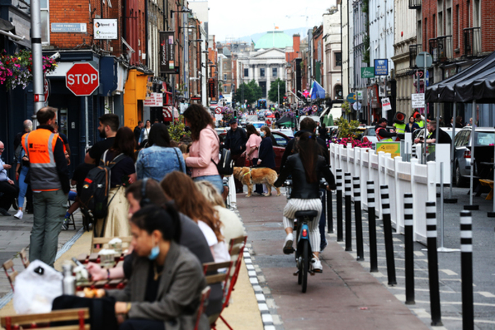 A busy street in Dublin with people sitting at tables and chairs on a path buildout that would have previously been a parking space. This has a black and white kerb at the edge, with a cycle lane running past that is protected by black and white plastic bollards. There are also people sitting at the side of a pub on chairs and standing talking near them. In the distance, there are people crossing the street, including a woman with a guide dog.