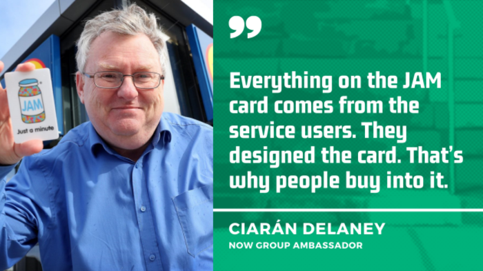 Ciarán Delaney, NOW Group Ambassador, wearing a blue shirt and holding a JAM card which has a drawing of a pot of jam and the writing 'Just a minute' on it, with the quote - Everything on the JAM card comes from the service users. They designed the card. That's why people buy into it.