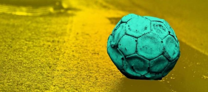 Design for Tough Start project - An old football that has too little air in it sitting on the side of the road.