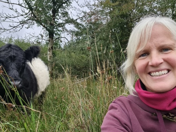 Farmer Nia O'Malley sitting on ground on her farm in Co Galway with her cows in the background