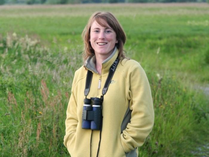 Kathryn Finney of BirdWatch Ireland wearing a yellow fleece standing in a field