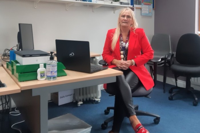 Mary Nevin wearing a red jacket sitting at her desk in front of her computer