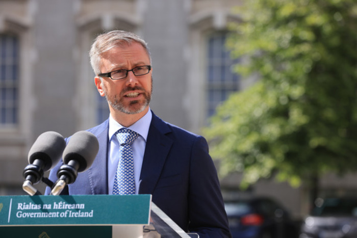 Minister Roderic O'Gorman - wearing a navy suit with light blue shirt and blue dotted tie - talking at a podium with two microphones on it.